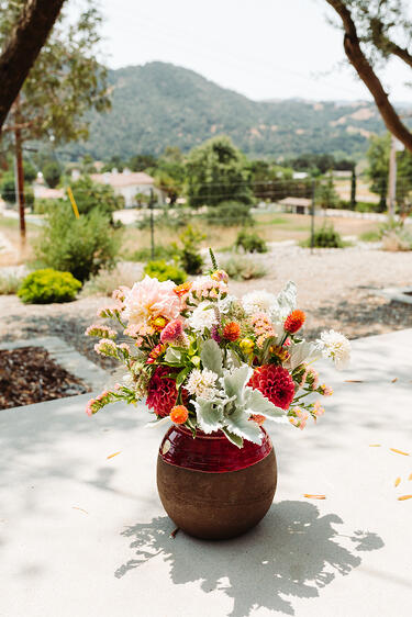 A bouquet of yellow, red, and orange flowers with greens sit in a red and brown jug on a cement table on The Starter Farm in California. The scene overlooks the Santa Ynez countryside.